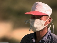 A_villager_from_Tae_Song_Dong_wears_a_mask_to_filter_out_dust_while_harvesting_rice_outside_of_the_village.jpg