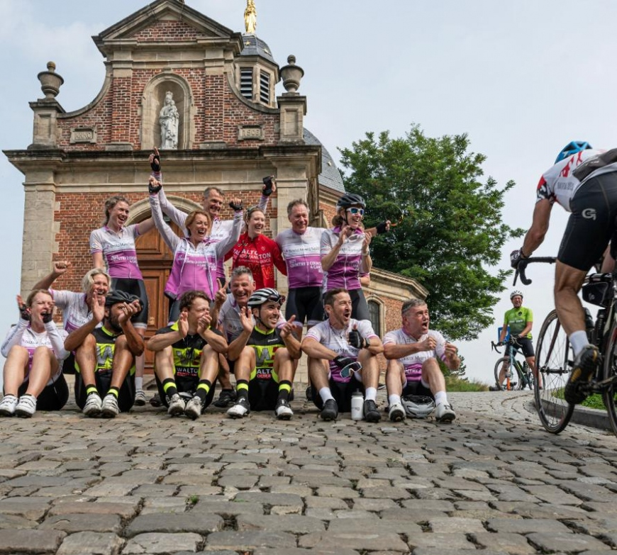 Riders of the Netherlands team in the C2C4C ride huddle in front of church to cheer other riders