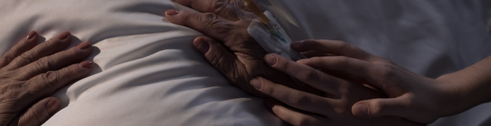 Close up of a hand touching a patient's hand on a bed