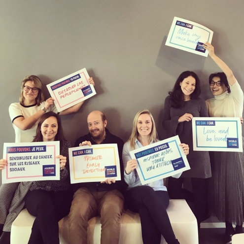 "UICC Comms Team holding their ""Signs for Change"""