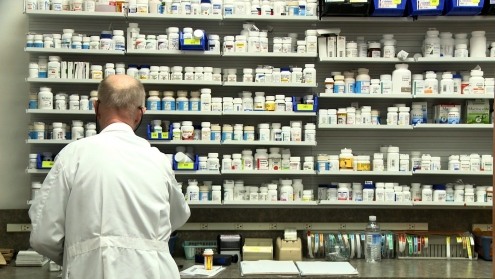 Pharmacist in front of medicine shelf