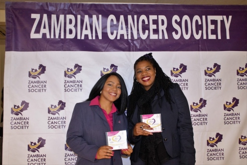 Zambia Cancer Society team members in front of branded backdrop