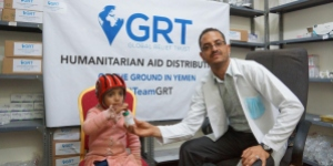 Doctor in Yemen posing with a child living with cancer in front of a billboard for aid distribution by the Global Relief Fund (GRT)