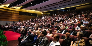 People seated in an auditorium listening to a session on cancer control