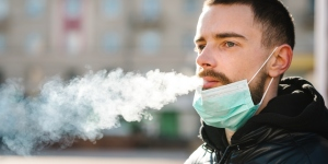 Man smoking with medical mask on his chin