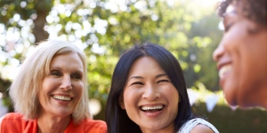 three women laughing in a park